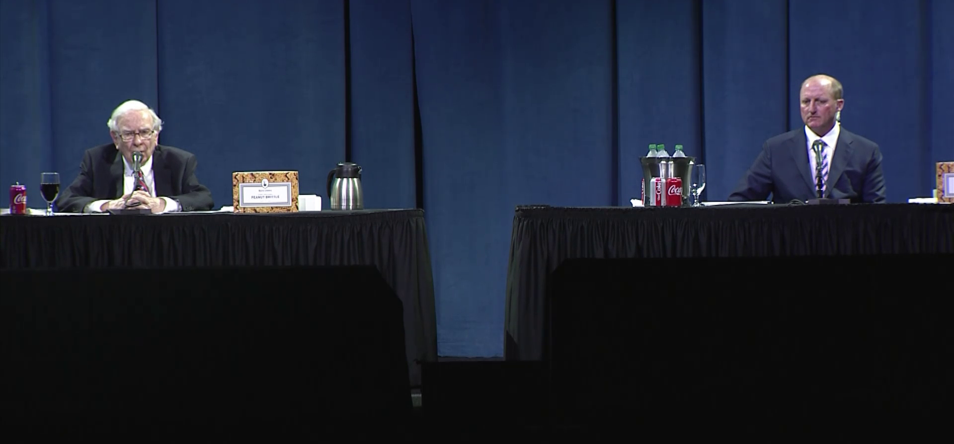 Warren Buffett and Greg Abel sit at separate tables at the 2020 Berkshire Hathaway annual meeting