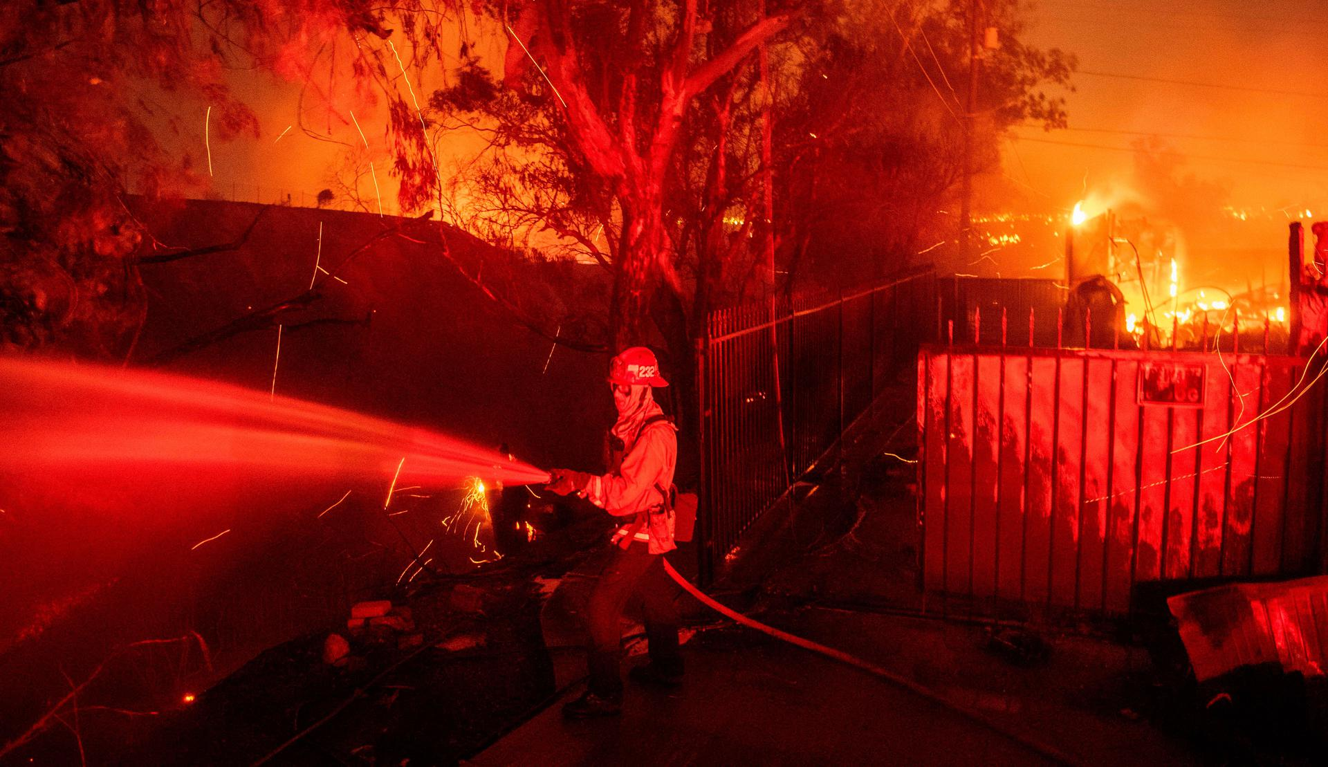 Firefighters battle wind-whipped flames engulfing multiple homes during the Hillside Fire in the North Park neighborhood of San Bernardino, California on October 31, 2019.  JOSH EDELSON / Contributor. AFP via Getty Images (1179184013)