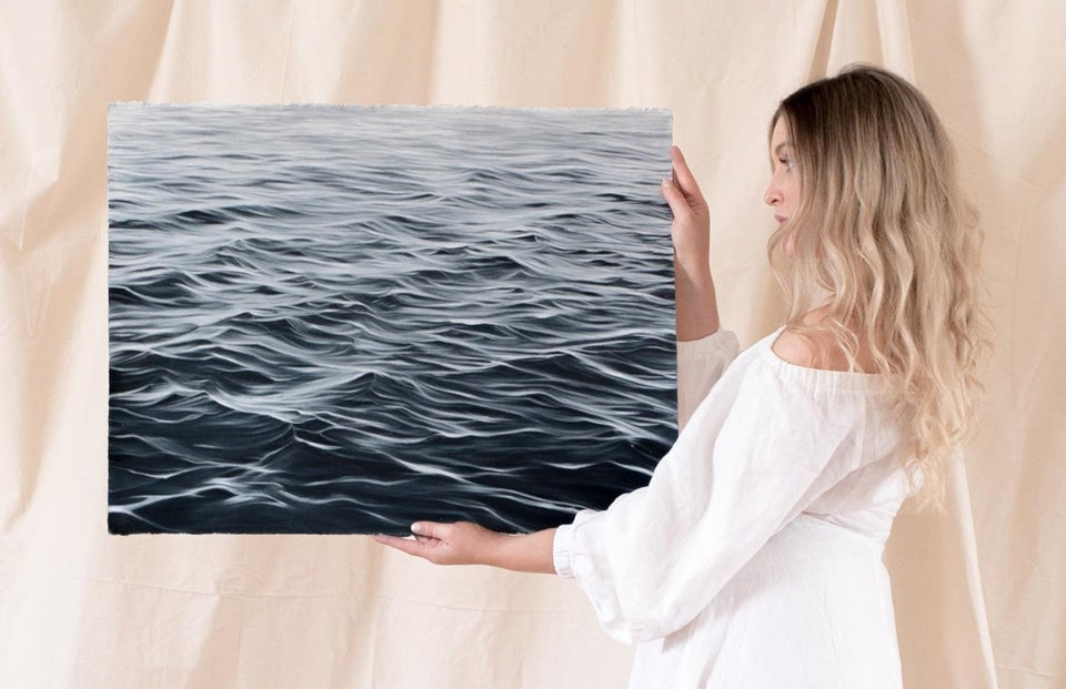 woman holding pencil drawing of ocean
