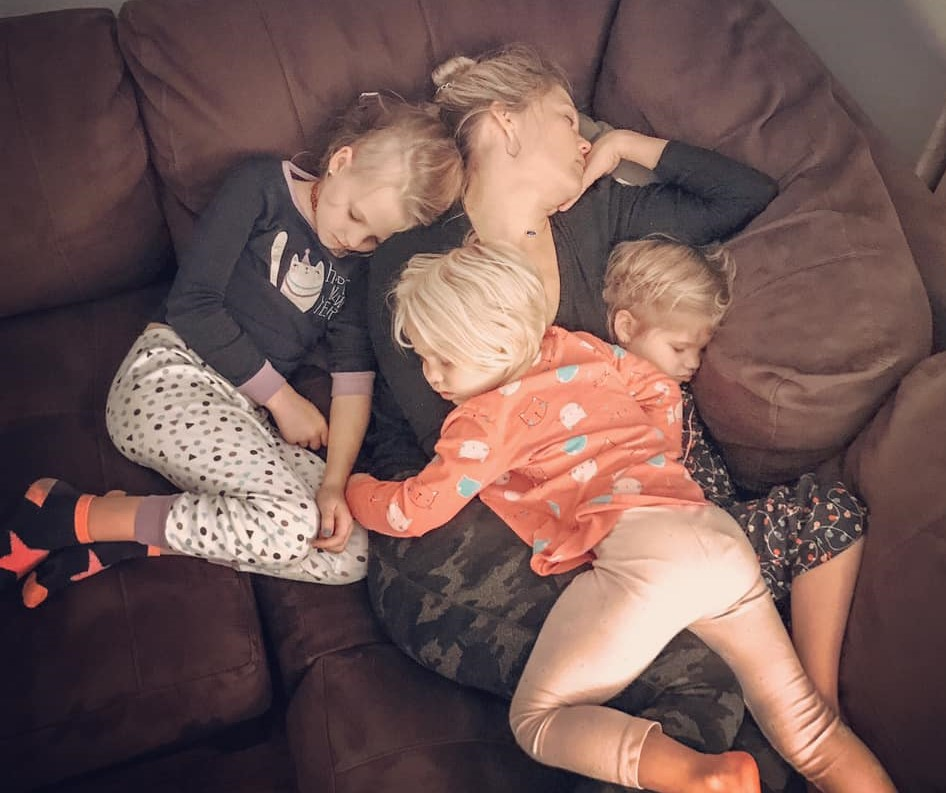 mom sleeping with children on top of her