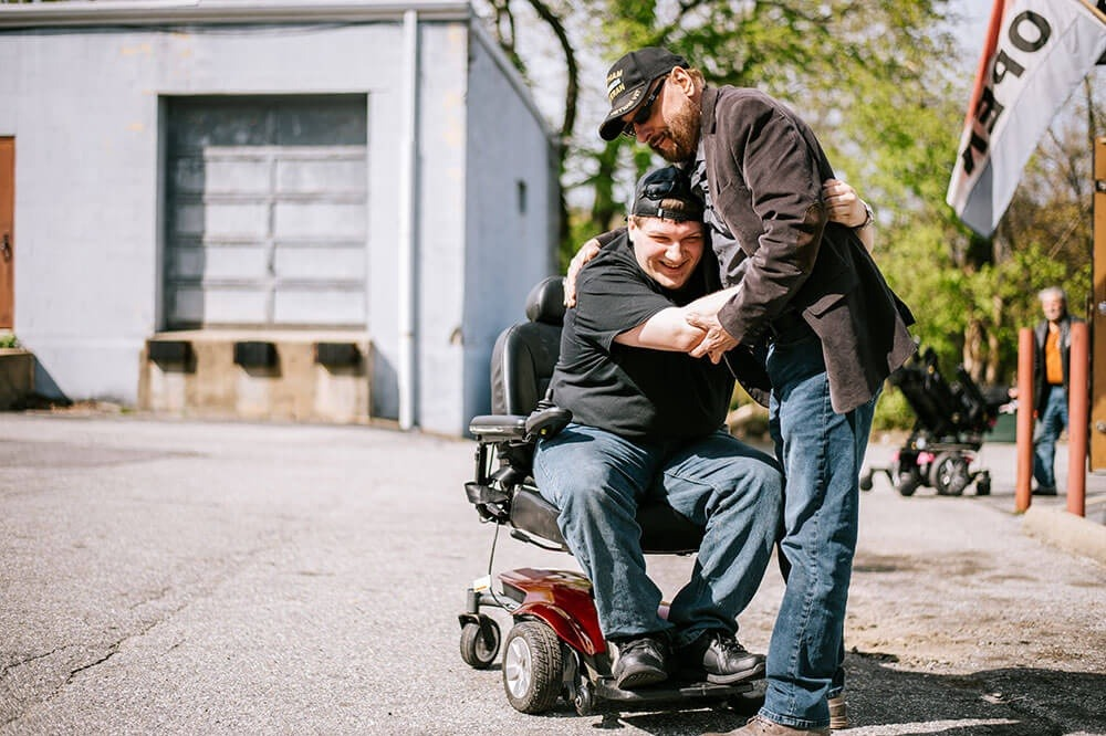 man in wheelchair hugging another man